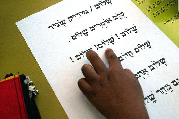 """RAMLA, ISRAEL - SEPTEMBER 1:  An Israeli first grade pupil looks for the word """"Shalom"""", which is Hebrew for peace, in the song """"Peace"""" by Mirik Snir, at a primary school on the first day of classes September 1, 2002 in the central Israel town of Ramla. Hundreds of thousands of Israeli children returned to school under tight security weeks before the current Israeli-Palestinian conflict enters its third year of mutual violence.  (Photo by David Silverman/Getty Images)"""