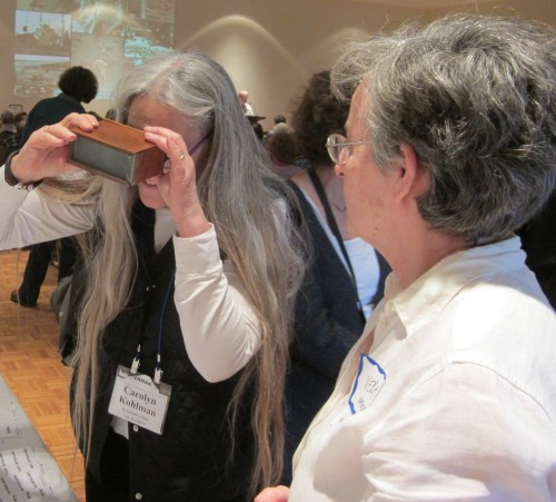 Carolyn Kohlman views Vera Meyer's family slides with 3-D viewer.