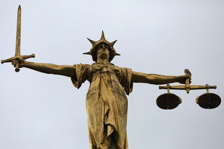 A statue of the scales of justice stands above the Old Bailey in London, England.  (Photo by Dan Kitwood/Getty Images)