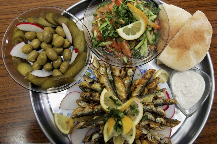 A meal of fried sardines with tahini sauce, fresh pita, a cucumber and tomato salad, olives and pickles is served in a restaurant in the local produce marketin Netanya, Israel. (Photo by David Silverman/Getty Images)