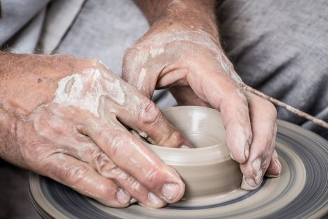 A man works with clay on a pottery wheel