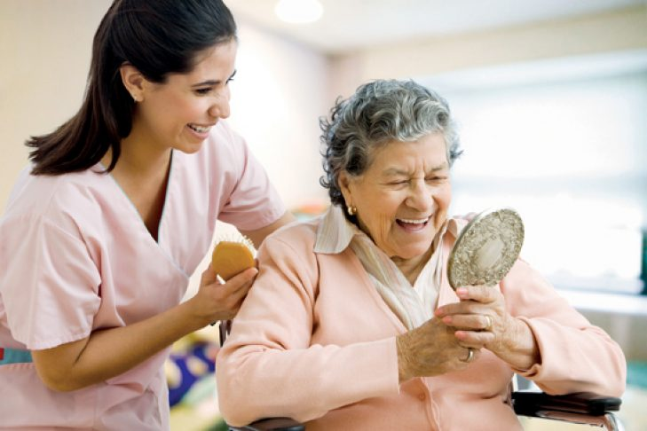 Hispanic nurse helping senior woman with hair