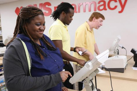 Jewish Vocational Service Transitions to Work career coach Noel Odaa, center, instructs Malika Jefferson, left, and Adam Palmer during their cashier internship training at CVS' Regional Learning Center. (Credit: Angela Rowlings)