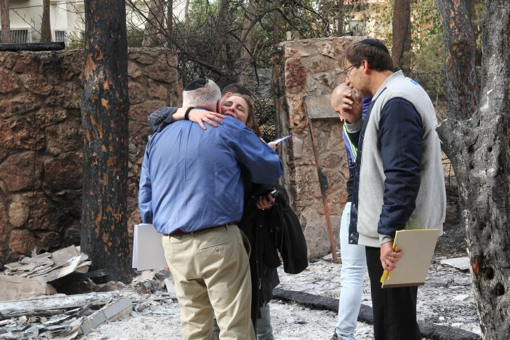 Barry Shrage, left, visits with Israelis impacted by the fires in Haifa.