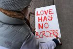Tori Furtado wrote a sign for a Boston rally that protested President Donald Trump's immigration policies on Saturday. (JOHN TLUMACKI/GLOBE STAFF)
