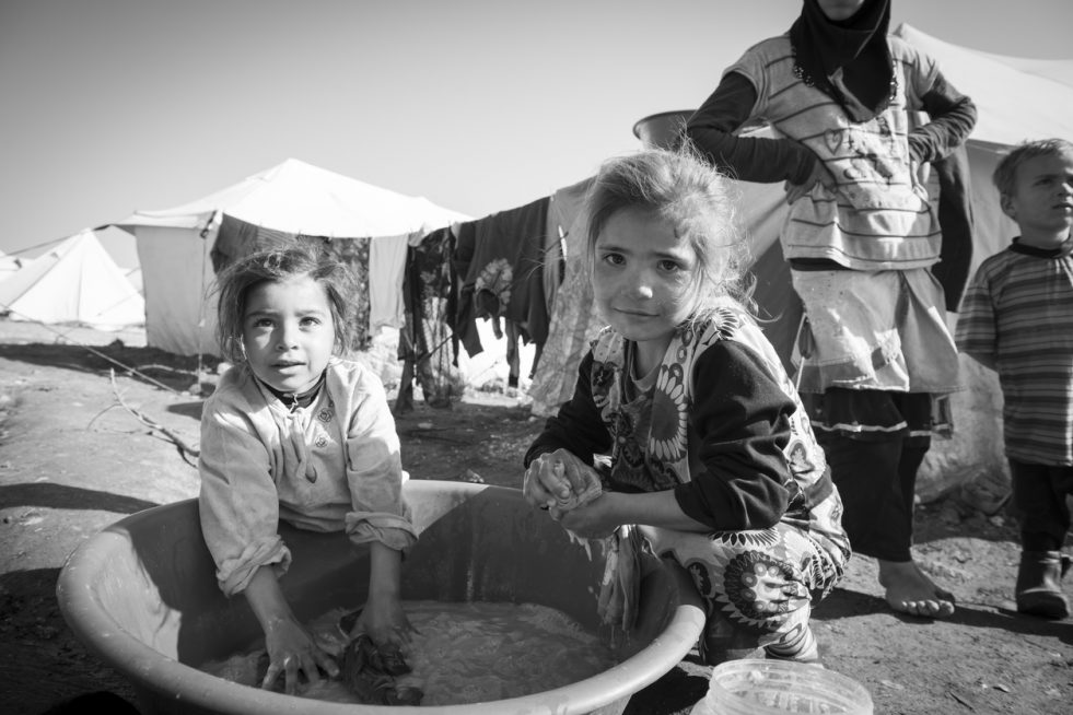 Two Syrian girls wash clothes outside their tent in the displaced persons camp in Atmeh, Syria, on Jan. 14, 2013. (Photo: Joel Carillet/iStock)