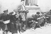 A group of men eating lunch, soup out of pails. (Henryk Ross/Art Gallery of Ontario, gift from the Archive of Modern Conflict/Courtesy Museum of Fine Arts)