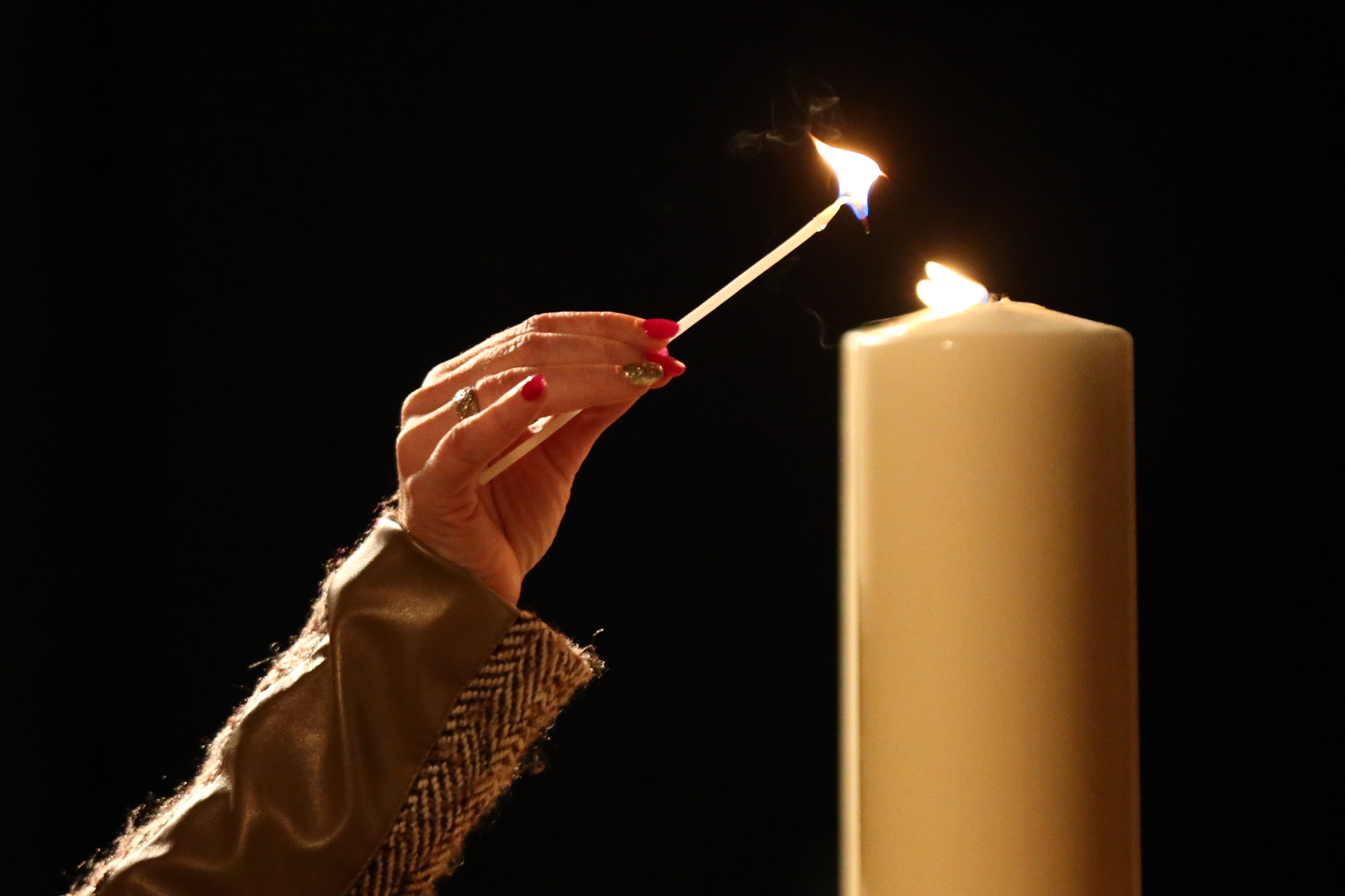 LONDON, ENGLAND - JANUARY 27: A woman lights a candle during an event to commemorate Holocaust Memorial Day at the Imperial War Museum on January 27, 2016 in London, England. Services have been held throughout Britain dedicated to the remembrance of those who suffered in The Holocaust and in subsequent genocides in Cambodia, Rwanda, Bosnia and Darfur. (Photo by Carl Court/Getty Images)