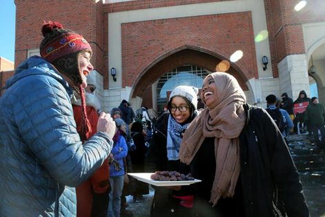 Sarah Kilgallon, of Watertown, accepted a date from worshippers Yusra Mukhtar and Nafisa Bilal outside the Islamic Society of Boston Cultural Center in Boston in February. (CRAIG F. WALKER/GLOBE STAFF)