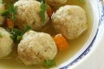 Close-up of matzo ball soup decorated with herbs and carrots