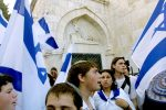 389592 16: Religious Jews carry flags as they pass under the Third Station of the Cross on the Via Dolorosa as they make their way through Jerusalem's Old City, May 21, 2001 during a Jerusalem Day march. Jerusalem Day is when the Jewish state celebrates the 1967 reunification of the city under Israeli rule during the Middle East War. (Photo by David Silverman/Getty Images)