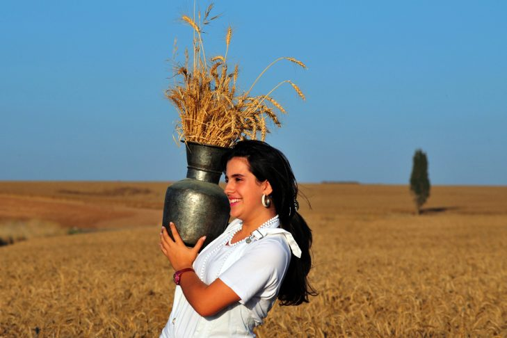 An Israeli woman celebrates Shavuot by carrying the first wheat harvest in a pitcher near Kiryat Gat, Israel. (Photo: chameleonseye/iStock)