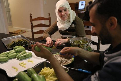 Asmaa made stuffed grape leaves with her husband in their kitchen. Abdulkader used bits of squash to practice his English letters, spelling out JFS, the acronym for his resettlement agency.