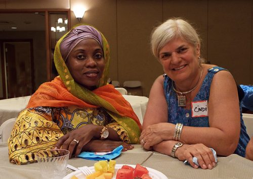 Faridah Lubega and Cindi Silverman enjoy a post-dinner conversation in the Congregation Beth Elohim social hall following the interfaith dinner.