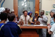 Rabbi Michael Rothbaum, flanked by community organizer Musa Mugenyi and Sheikh Rajab Mayanja, unrolls a Jewish Torah scroll for the Ugandan-American Muslim visitors to Congregation Beth Elohim.