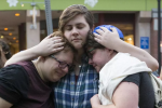 From left to right, Sasha Kaufman, Roni Simcha Miller and August Eberlein, embrace after a vigil at the Holocaust Memorial. (NICHOLAS PFOSI FOR THE BOSTON GLOBE)