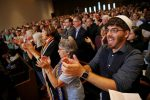 Bryan Mann, a rabbinical school student, applauded comments from Attorney General Maura Healey during the Interfaith Gathering of Unity, Love, and Strength at Temple Israel of Boston. (CRAIG F. WALKER/GLOBE STAFF)