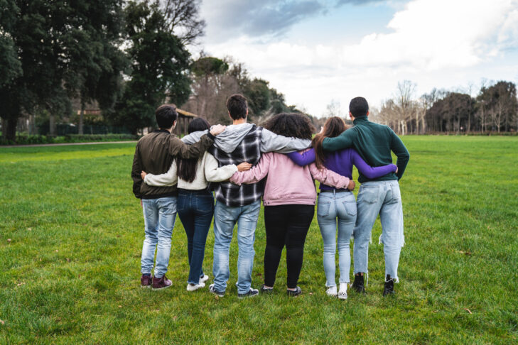 Group of six teenager friends embracing together at the park, rear view. Teamwork and cooperation concept with people together, sharing a common purpose.