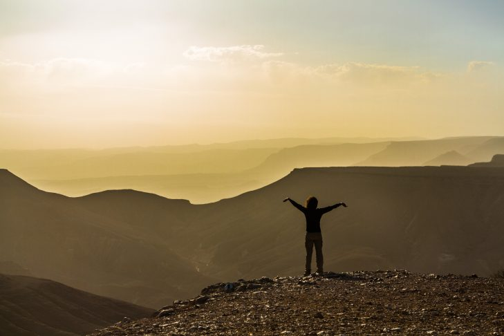 A hiker on top of a hill in the Israeli desert near the town of Sde Boker, part of the Israel National Trail (Courtesy Udi Goren)