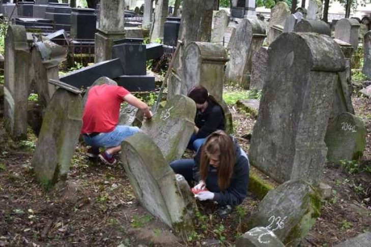 High school students from the Tarnow Matzevot (volunteer camp) chalk and identify Jewish cemetery gravestones to make a catalogue available online to families around the world. (Courtesy photo)