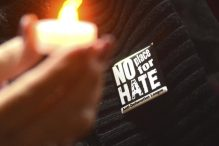 Referral use only - Holding electric votives and wearing pins from the Anti-Defamation League, about 600 attend a gathering at Knesset Israel in Pittsfield, Mass. for an Interfaith Community Vigil on Thursday, Nov.  1, 2018, honoring the lives lost at the Tree of Life Synagogue in Pittsburgh. (Gillian Jones/The Berkshire Eagle via AP)