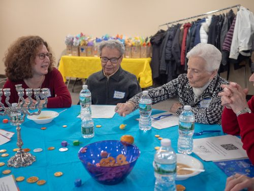 Guests at the Friendly Visitor Chanukah Celebration playing dreidel