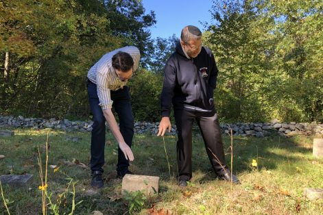 REFERRAL: Historian Alex Green, left, and Gann Academy teacher Yoni Kadden point to a grave marker in Waltham's Metfern Cemetery. (Eve Zuckoff for WBUR)