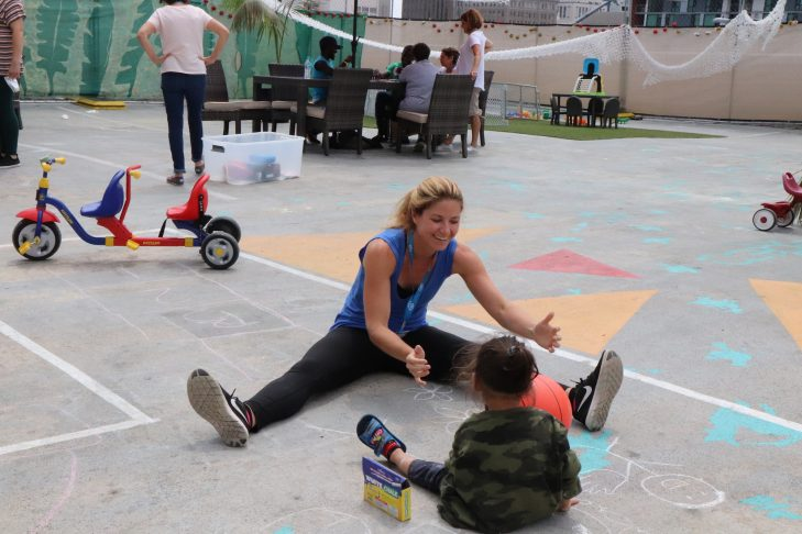 Lucia Carballo Panichella plays with a child in San Diego (Photo: Craig Byer/CJP)