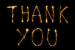 close up view of thank you light lettering on black backdrop
