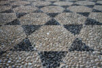 Floor mosaic of gray and black stones in the form of six-pointed stars.