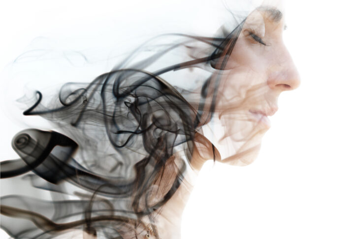 Double exposure photograph of a young woman combined with an image of the smoke