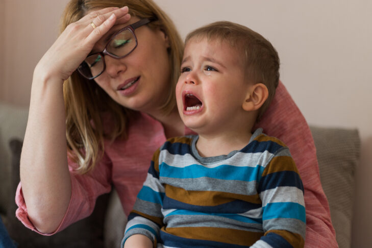 Tired, desperate mother is holding her two year old son, crying.Negative human emotion face. Upset toddler boy. Problem child. Depression, stress or frustration.