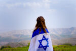 Little patriot jewish girl standing and enjoying great view on the sky, valley and mountains with the flag of Israel wrapped around her. Memorial day-Yom Hazikaron and Yom Ha'atzmaut concept.
