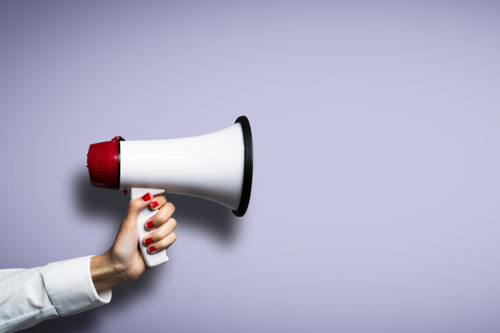 hand with a megaphone in front of an empty background