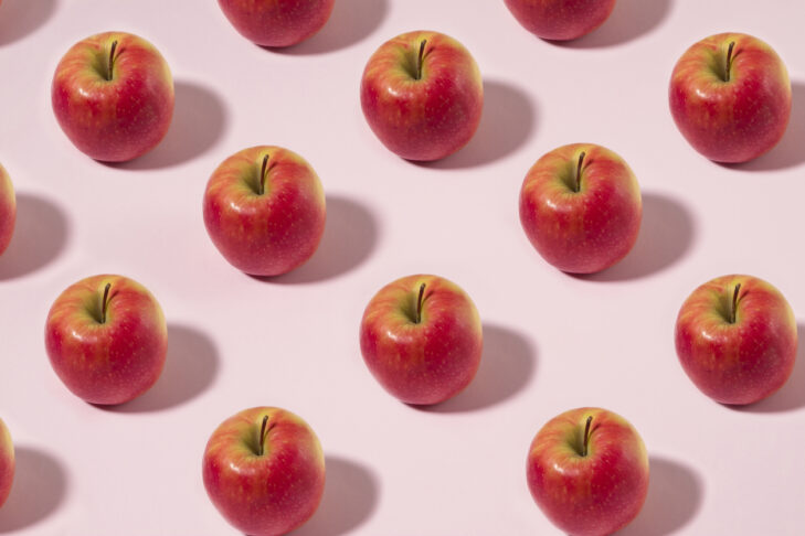 Red apple fruit in a row on pink pastel background