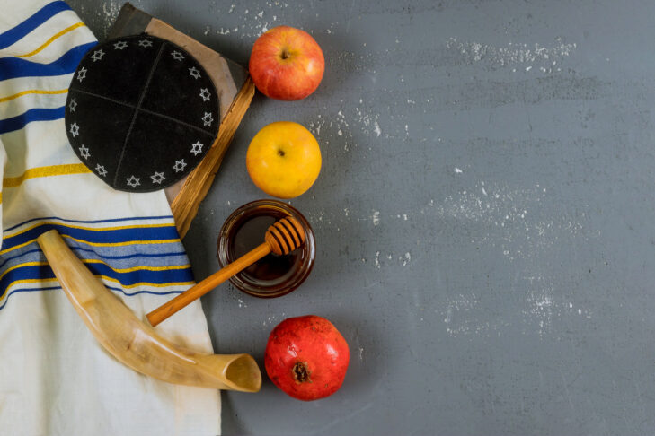 Jewish holiday honey and apples with pomegranate torah book, kippah a yamolka talit copy space