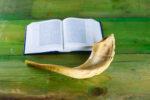 Rosh Ha Shana- Jewish new year, Yom Kippur composition of an Torah and Shofar horn on rustic wood green background.