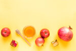 Rosh Hashanah (Jewish New Year holiday) concept. Traditional symbols - apples, honey, pomegranate on yellow background, top view, copy space.