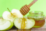 Jewish holiday, Apple Rosh Hashanah, on the photo have honey in jar and drop honey on green apples on wooden with green background