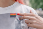 Female hand with red nails points to lgbt sign. LGBTQ, lgbt gay pride tolerance concept.