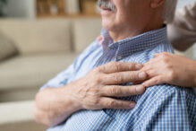 Hands of young daughter and that of her retired senior father on his shoulder as expression of love, affection and care