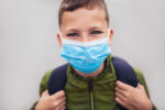 Child wear facemask during coronavirus and flu outbreak. The boy wear a mask before going to school preventing outbreak Infectious disease and dust in the air.