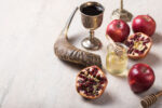 Rosh hashanah - jewish New Year holiday concept. Traditional symbols: Honey jar and fresh apples with pomegranate and shofar-horn,  on a concrte   background. Copy space for text. View from above