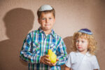 The Jewish holiday of Sukkot. Two boys in yarmulkes. The older boy is holding the etrog