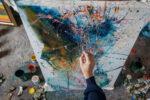 Artist- painter working on painting in studio with art supplies around him