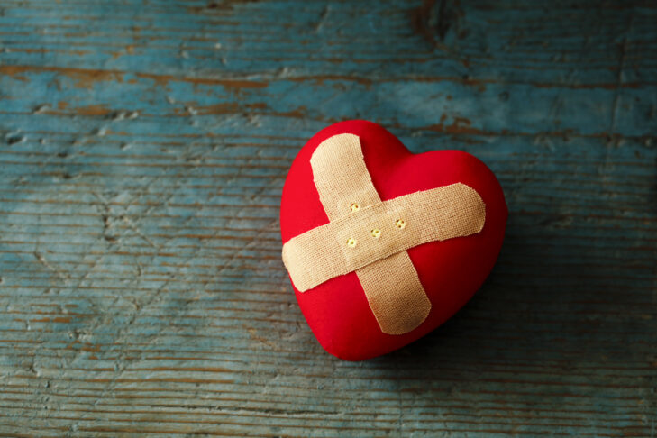 Band-aid covering a heart on a blue wooden background