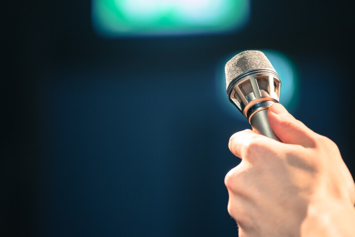 Young man on the stage is talking into a microphone, speech