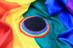 Rainbow colored yarmulke over rainbow flag