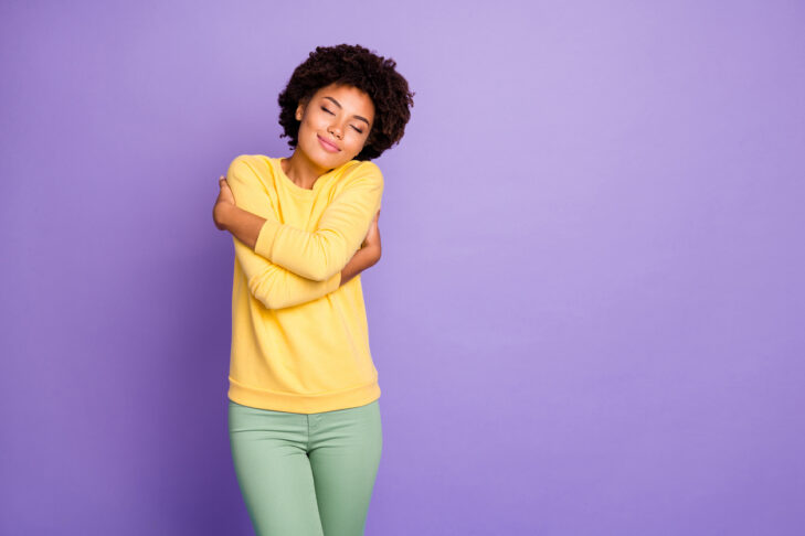 Portrait of her she nice attractive charming lovely dreamy cheerful cheery, wavy-haired girl hugging herself peaceful isolated over violet purple lilac pastel color background
