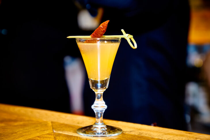 Shot with Limoncello in a glass on a high leg is on the bar.